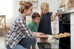Madre y sus ni?os que sacan las galletas del horno imagenes de archivo