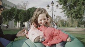 Madre y sus pequeñas hijas adentro al aire libre Mamá feliz y niño de la familia que se besan y que abrazan almacen de video