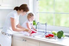 Madre y sus verduras que se lavan de la hija del niño imagenes de archivo