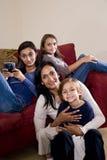 Madre y tres niños que se sientan en el país junto Imagen de archivo