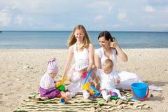 Madres felices con los niños en la playa Imágenes de archivo libres de regalías