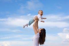Madres felices con los niños en la playa imagenes de archivo