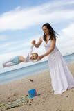 Madres felices con los niños en la playa Imagen de archivo libre de regalías
