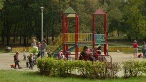 Madres jovenes con los niños en patio D3ia del otoño Tiro liso del carro metrajes