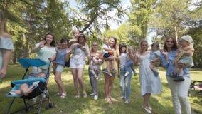 Madres jovenes con los niños y los cochecitos en el parque Mire la cámara y agitar metrajes