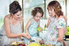 Madres jovenes que hacen una torta con sus hijas Imagen de archivo
