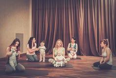 Madres jovenes y sus bebés que hacen ejercicios de la yoga en las mantas en el estudio de la aptitud Foto de archivo