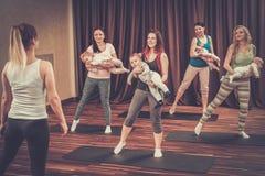 Madres jovenes y sus bebés que hacen ejercicios de la yoga en las mantas en el estudio de la aptitud Foto de archivo libre de regalías