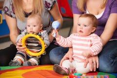 Madres y bebés en el grupo de la música foto de archivo