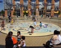 Madri e bambini alla sosta dell'acqua Immagini Stock Libere da Diritti