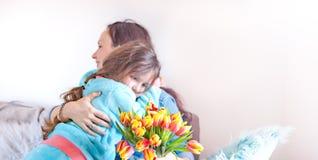 Madri e derivati delicati degli abbracci, congratulazioni sulla festa e fiori Concetto della cartolina d'auguri di giorno del ` s immagini stock libere da diritti