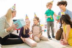 Madri ed ipotesi dei bambini che cosa è interno del contenitore di regalo fotografia stock