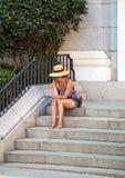 2017 05 31, Madri, Espanha Povos na rua do Madri Um chapéu vestindo e óculos de sol da mulher que sentam-se nas escadas fotos de stock