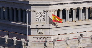 Madrid day light roof top clock and waving national flag 4k spain stock footage