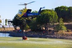 MADRID, ESPAÑA - 3 DE AGOSTO: Encienda el helicóptero pesado del rescate con el cubo de agua, va a un fuego en Madrid el 3 de agos Imágenes de archivo libres de regalías