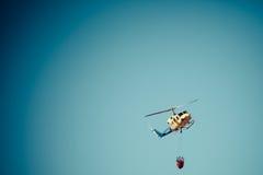 MADRID, ESPAÑA - 3 DE AGOSTO: Encienda el helicóptero pesado del rescate con el cubo de agua, va a un fuego en Madrid el 3 de agos Fotos de archivo