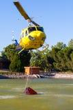 MADRID, ESPAÑA - 3 DE AGOSTO: Encienda el helicóptero pesado del rescate con el cubo de agua, va a un fuego en Madrid el 3 de agos Foto de archivo libre de regalías