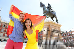 Madrid people showing Spain flag on Plaza Mayor. Cheerful and happy in Spain. Cheering celebrating young women and men holding and showing flags to camera on stock image