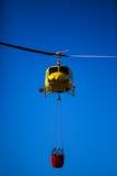 MADRID, SPAGNA - 3 AGOSTO: Inforni l'elicottero pesante di salvataggio con il secchio di acqua, va ad un fuoco a Madrid il 3 agost fotografia stock