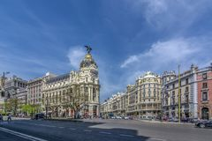 Metropolis hotel in Madrid in a beautiful spring day, Spain. Madrid, Spain, April 2017 : Gran Via and the iconic Metropolis Building sourrounded by trational royalty free stock photos