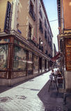 MADRID, SPAIN - APRIL 26: Old narrow street with few cafe in Apr Stock Photo