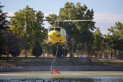 MADRID, SPAIN - AUGUST 3 : Fire rescue heavy helicopter with water bucket, goes to a fire in Madrid on August 3, 2013, Spain. Royalty Free Stock Photos