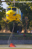 MADRID, SPAIN - AUGUST 3 : Fire rescue heavy helicopter with water bucket, goes to a fire in Madrid on August 3, 2013, Spain. Royalty Free Stock Photography