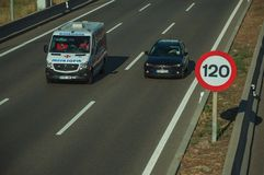 Car and ambulance on highway and SPEED LIMIT sign in Madrid royalty free stock photography
