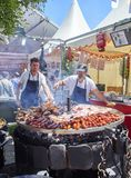 Cooks cooking Sausages and Pork Ribs on a charcoal bbq. Madrid, Spain - May 15, 2018. Hispanic cooks cooking Sausages Pork Spare Ribs and others meats on a royalty free stock photos