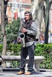 Madrid, Spain - The musician in a park. MADRID, SPAIN - APRIL 04: This performer - musician plays jazz songs on a saxophone in a park in central of Madrid, Spain Stock Image