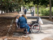 Free Madrid, Spain, October 9, 2019 . Care Worker With Elderly Lady On The Bench In Park.Wheelchair Near Stock Images - 163996194