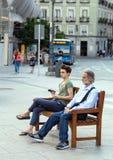 2017 05 31, Madrid, Spanien Leute auf der Straße von Madrid Ein alter Mann und ein Junge, die auf der Bank in der Straße sitzen R stockfotografie