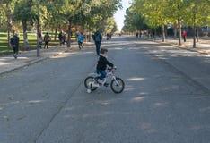 Madrid Spanien - November 12,2017: Det unga oidentifierade barnet rider cykeln i Retiro parkerar Madrid, Spanien arkivfoto