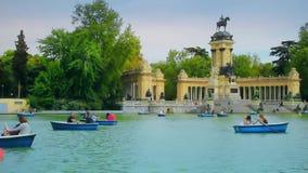 Madrid, Spanje - April 2018: Toeristen en stadslui de rust en zwemt in boten Park Buen Retiro - stadspark in het centrum stock videobeelden