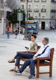 2017 05 31, Madrid, Spanje Mensen op de straat van Madrid Een oude mens en een jonge jongenszitting op de bank in de straat Oproe stock foto's