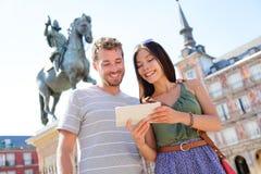 Madrid-Touristen, die Tablettenreise-APP verwenden Stockfotos