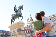 Madrid tourists on Plaza Mayor looking at statue. Of King Philip III. Travel couple sightseeing visiting tourism landmarks and attractions in Spain. Young women stock image