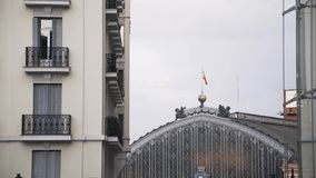 Madrid train station with a clock and a flag. View of Madrid train station. Spanish flag in the wind. Large clock is seen in the background. People are passing stock footage