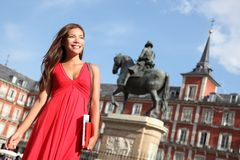 Madrid - Woman on Plaza Mayor. Madrid. Woman tourist walking on Plaza Mayor Madrid, Spain. Beautiful woman in red dress. Tourist attraction, statue of Felipe III stock photography