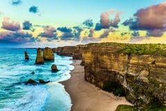 Madrugada en la costa del océano las nubes que han dado vuelta rosado en el amanecer sobre las rocas bien conocidas a doce apósto foto de archivo libre de regalías