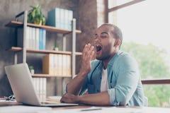 Madrugada en la oficina El freelancer cansado soñoliento está bostezando en su lugar de trabajo delante de la pantalla del ` s de fotos de archivo libres de regalías