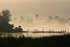 Madrugada en un lago con la niebla Imágenes de archivo libres de regalías