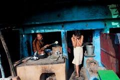 Madrugada en una familia india, padre que prepara el desayuno Imagenes de archivo