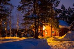 Madrugada y cabaña de madera en el bosque del invierno Fotografía de archivo