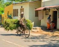 MADURAI, ΙΝΔΙΑ - 17 ΦΕΒΡΟΥΑΡΊΟΥ: Το ινδικό αγροτικό άτομο οδηγά ένα ποδήλατο α Στοκ Εικόνες