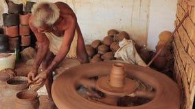 Madurai, Индия - 20180310 - человек использует полностью ручное колесо гончара - мочит глину и начинает отрезать сток-видео