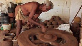 Madurai, Индия - 20180310 - человек использует полностью ручное колесо гончара - строения вверх по глине сток-видео