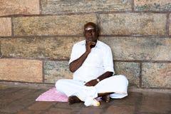 MADURAI, ИНДИЯ - 16-ОЕ ФЕВРАЛЯ: Неопознанный человек сидя на Стоковая Фотография