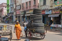 Worn tires on the move. Madurai, India – March 9, 2018: Unidentified porter transporting a load of worn tyres through the city centre. Porters are used to Royalty Free Stock Photography