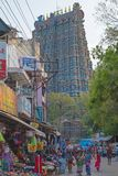 Bustling streets below a Hindu temple gateway. Madurai, India - March 8, 2018: Bustling street scene below the eastern Gopuram, or entrance gateway, to the 14th royalty free stock photos